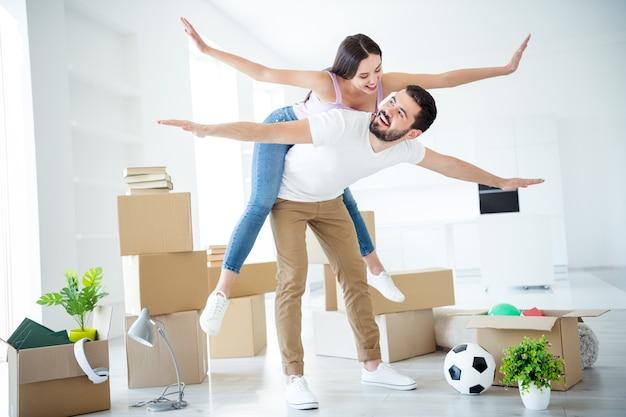 Вид в полный рост красивой привлекательной веселой игривой пары, держащей в руках летающий самолет, аренда недвижимости, аренда, кредит, безопасность, страхование имущества, путешествие, поездка в светлый белый интерьер дома