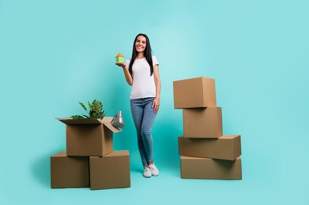작은 집을 들고 해외로 이사하는 멋진 매력적인 쾌활한 성공적인 brunet 소녀의 전체 길이 몸 크기보기