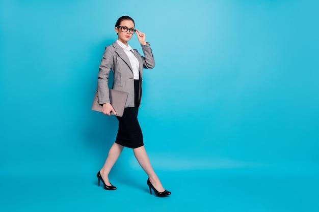 Полноразмерный вид красивой привлекательной леди-работодателя с ноутбуком, изолированной на ярко-синем цветном фоне