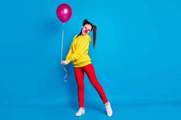 밝고 선명한 파란색 배경에서 격리된 채 즐겁게 포즈를 취하는 헬륨 공을 손에 들고 있는 멋지고 수줍은 쾌활한 소녀 서커스 광대의 전신 크기