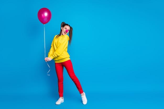 밝고 선명한 파란색 배경에서 격리된 즐거운 시간을 보내는 공기 공을 손에 들고 있는 멋지고 재미있고 유쾌한 쾌활한 소녀 광대의 전체 길이 신체 보기