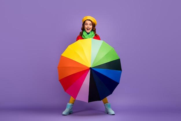 Вид в полный рост красивой привлекательной радостной позитивной веселой веселой волнистой девушки, держащей вращающийся радужный зонтик, развлекающейся, изолированной на фиолетово-сиреневом пурпурном пастельном цветном фоне