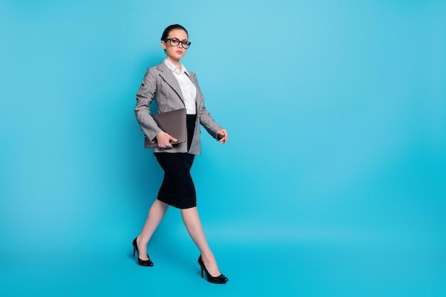 Вид в полный рост симпатичной привлекательной леди-лидера с ноутбуком, идущей на встречу, изолированной на ярко-синем цветном фоне