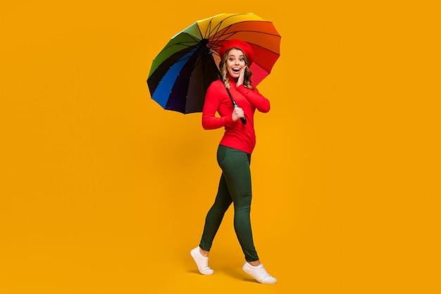 Вид в полный рост красивой привлекательной милой удивленной веселой веселой волнистой девушки, держащей в руке зонтик, идущей веселиться, изолированной на ярком ярком сияющем фоне яркого желтого цвета