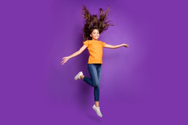 Вид в полный рост красивой привлекательной милой очаровательной довольно жизнерадостной веселой волнистой девушки, прыгающей и веселой весенней прогулки, изолированной на сиреневом фиолетовом фиолетовом пастельном цветном фоне