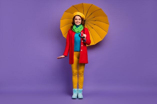 Вид в полный рост красивой привлекательной милой очаровательной довольно модной веселой веселой скромной волнистой девушки, держащей зонтик, позирующей изолированно на фиолетово-сиреневом пурпурном фоне пастельных тонов