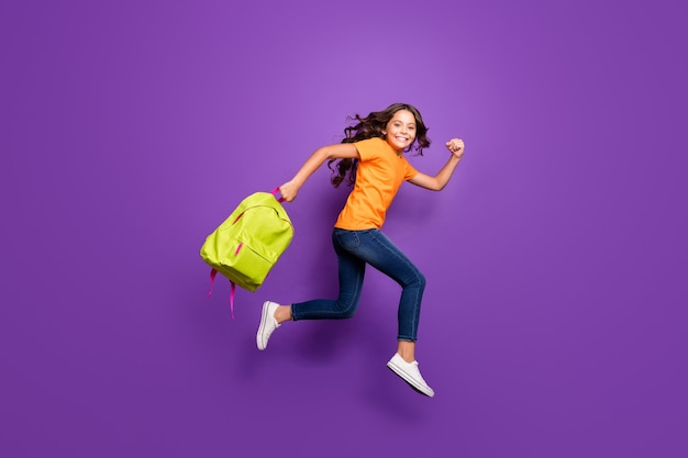 Вид в полный рост красивой привлекательной милой веселой веселой волнистой девушки, прыгающей в сумке для переноски, бегущей осенней осенью 1 первого сентября, изолированной на сиреневом фиолетовом фиолетовом пастельном цветном фоне
