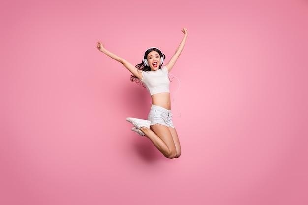 좋은 매력적인 사랑스러운 맞는 슬림 펑키 꿈꾸는 쾌활한 쾌활한 물결 모양의 소녀 점프의 전체 길이 몸 크기보기 재미 듣기 멜로디 히트 노래 핑크 파스텔 컬러 벽 위에 절연
