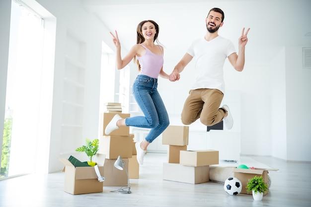 Вид в полный рост красивой привлекательной милой радостной веселой счастливой пары, прыгающей с удовольствием, показывающей страхование имущества безопасности ссуды с v-образным знаком в светло-белой внутренней квартире дома
