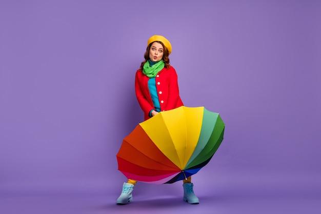 Вид в полный рост красивой привлекательной милой довольно веселой веселой волнистой девушки, держащей в руках радужный зонтик, отправляющей воздушный поцелуй на фиолетово-сиреневом фиолетовом фоне пастельных тонов
