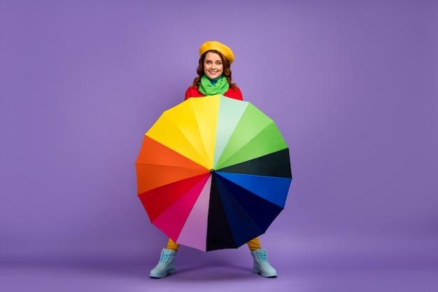 Вид в полный рост красивой привлекательной милой довольно веселой веселой волнистой девушки, держащей вращающийся зонтик, развлекающейся, изолированной на фиолетово-сиреневом фиолетовом пастельном цветном фоне