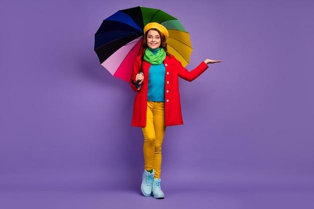 Вид в полный рост красивой привлекательной милой довольно веселой волнистой девушки, держащей зонтик с копией пространства на ладони, проверяющей каплю дождя, изолированную на фиолетово-сиреневом пурпурном пастельном цветном фоне