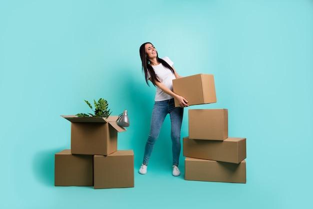 Вид в полный рост красивой привлекательной грустной измученной брюнетки, переезжающей за границу, держащей в руках большую большую коробку, изолированную на ярком ярком блеске, ярком бирюзовом зеленом синем бирюзовом цвете