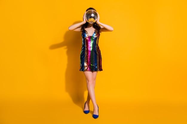 Вид в полный рост красивой привлекательной стройной девушки с волнистыми волосами, весело держащей в руке серебряный шар, пряча лицо ночная жизнь, изолированный яркий яркий блеск яркий желтый цвет фона