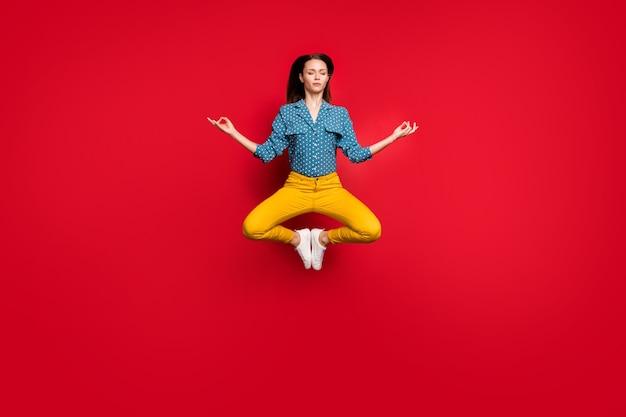 격리된 밝은 붉은 색 배경을 명상하는 옴 기호를 보여주는 앉아 있는 연꽃 포즈를 취하고 있는 침착한 집중된 소녀의 전체 길이 신체 크기 보기