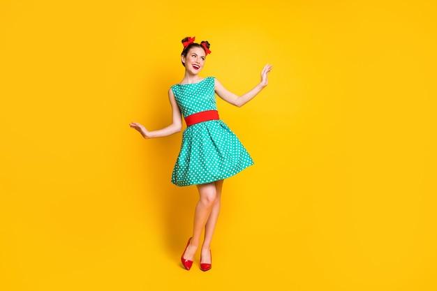 Вид в полный рост красивой очаровательной жизнерадостной девушки в бирюзовом платье, танцующей, позирующей, изолированной на ярко-желтом цветном фоне