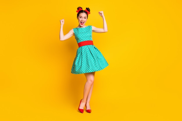 Вид в полный рост симпатичной жизнерадостной девушки в бирюзовом платье, развлекающейся празднованием на ярко-желтом фоне