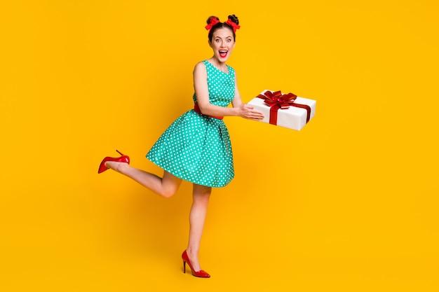 Вид в полный рост симпатичной жизнерадостной девушки в бирюзовом платье, держащей подарочную коробку за руки, развлекающейся на фоне ярко-желтого цвета