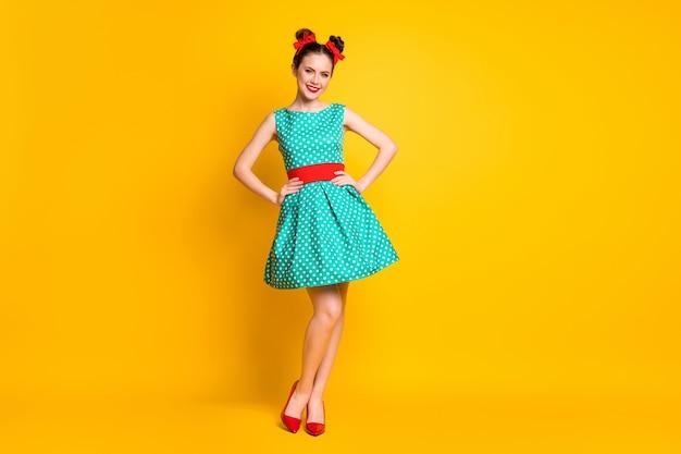 Вид в полный рост симпатичной жизнерадостной девушки в платье с бирюзовыми точками, позирующей руки на бедрах, изолированных на ярко-желтом цветном фоне