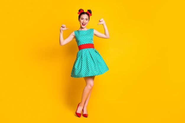 Вид в полный рост красивой элегантной жизнерадостной девушки в бирюзовой одежде, демонстрирующей себя изолированной на ярко-желтом фоне