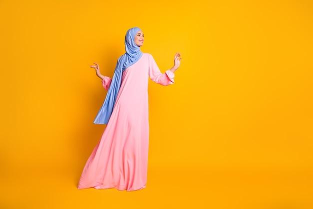 선명한 노란색 배경에 격리된 멋지고 쾌활한 여성 이슬람교도 워킹 카피 공간의 전체 길이 신체 크기