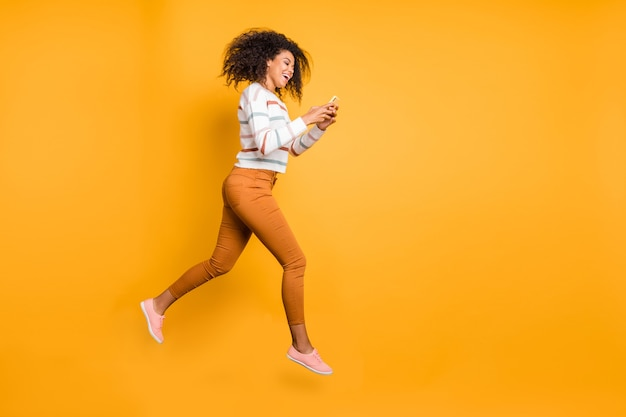 5gアプリのデジタル電話を使用してジャンプする素敵な女の子の全身サイズのビュー
