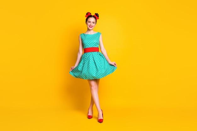 Вид в полный рост красивой довольно стройной жизнерадостной девушки в бирюзовом платье, идущей изолированно по ярко-желтому цветному фону