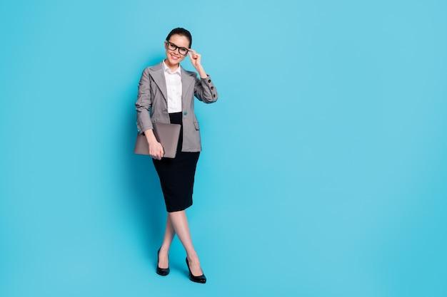 ラップトップに触れてスペックを分離された鮮やかな青い色の背景を手に持っている素敵なスマートで陽気な女の子の専門家の全身サイズのビュー
