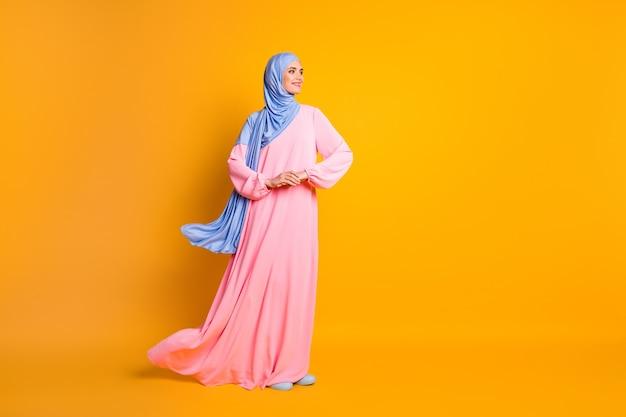 밝은 노란색 배경에 격리된 히잡 드레스를 입은 꽤 쾌활한 여성 무슬림의 전신 크기 보기