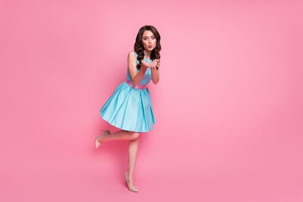 Красивая девушка позирует в полный рост, отправляя воздушный поцелуй, изолированный розовый цвет фона