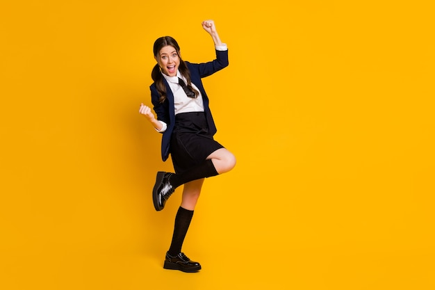 Full length body size view of overjoyed lucky cheery schoolgirl celebrating excellent mark