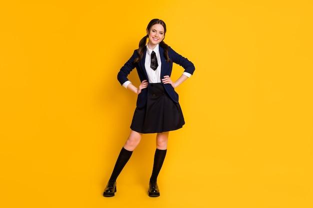 Full length body size view of pretty cheerful schoolgirl posing