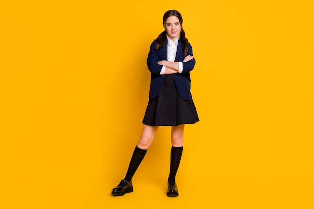 Full length body size view of pretty content schoolgirl folded arms