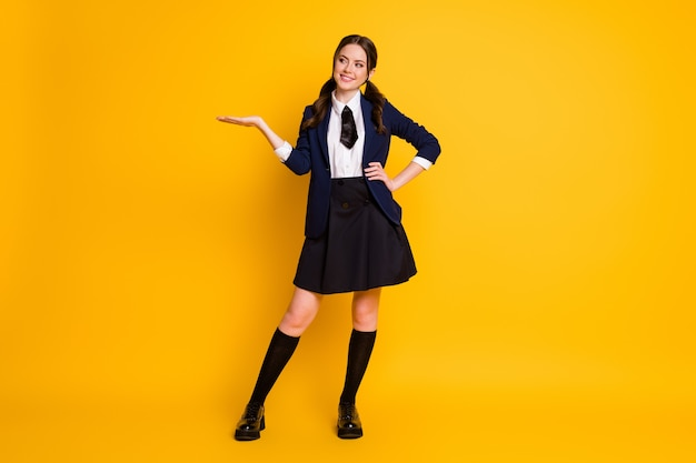 Full length body size view of schoolgirl holding on palm copy empty blank space