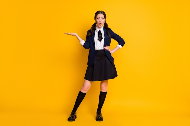 Full length body size view of stunned schoolgirl holding on palm copy space novelty advert
