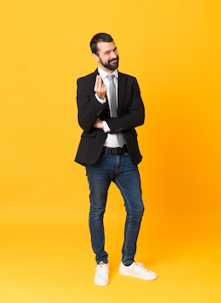 Full length  of business man over isolated yellow wall making money gesture