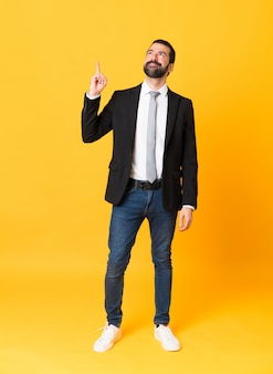 Full length  of business man over isolated yellow wall pointing up and surprised