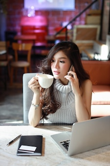 Full length business selling online, young asian woman in casual dress working on computer