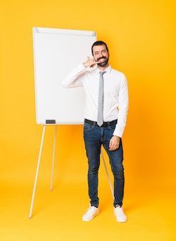 Full length  businessman giving a presentation on white board over isolated yellow wall making phone gesture. call me back sign