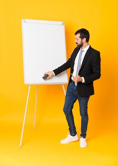 Full length  of businessman giving a presentation on white board over isolated yellow wall