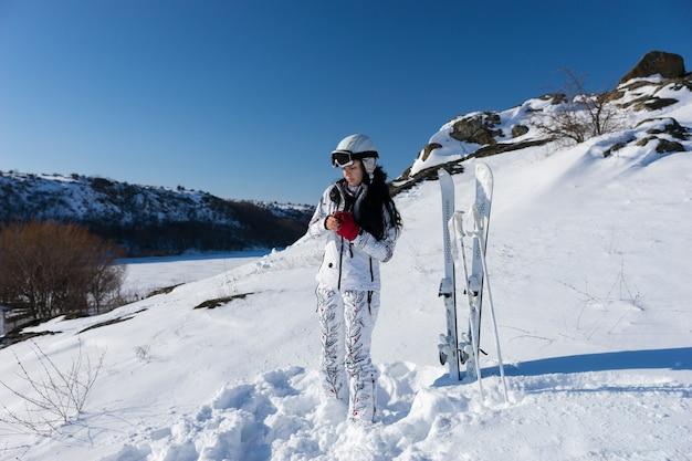 В полный рост молодая женщина в белом лыжном костюме и шлеме, надевает красные перчатки и стоит рядом с лыжами и палками на заснеженном склоне горы в яркий день с теплым солнцем и голубым небом