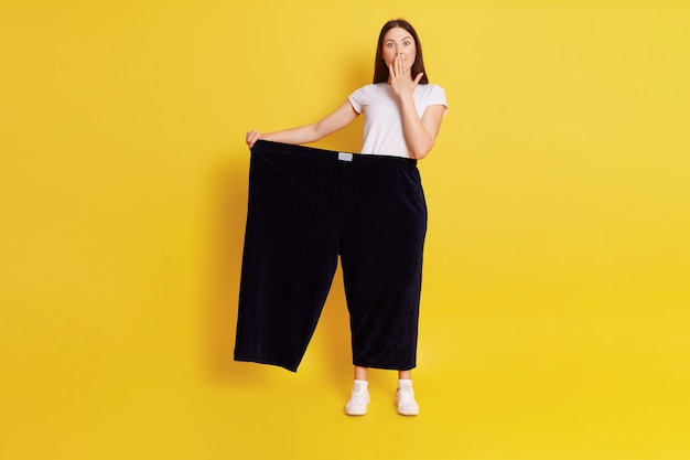 Full length of caucasian astonished female lost weight and wearing old pants, being shocked and covering mouth with palm, posing isolated over yellow wall.