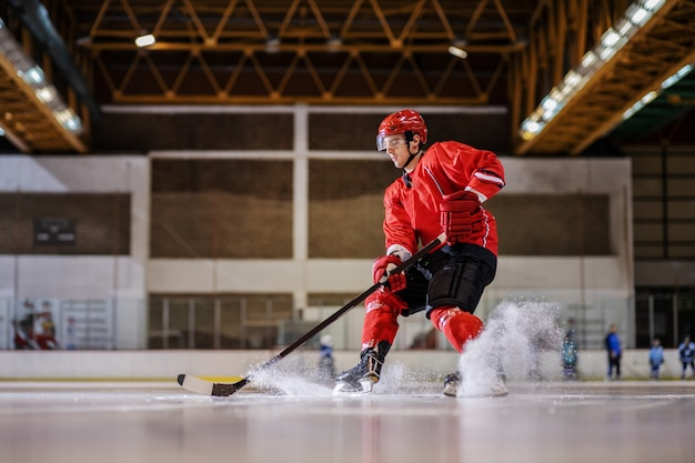 Full length of caucasian hockey player playing hockey on ice in hall.
