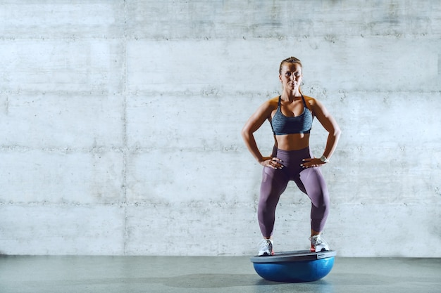 Full length of caucasian sportswoman in sportswear with ponytail standing on bosu ball and doing squat endurance