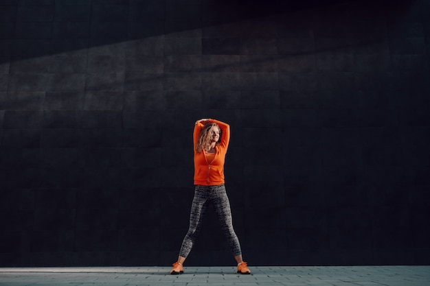 Full length of charming fit caucasian woman in sportswear and curly hair standing in front of black wall and stretching arm.