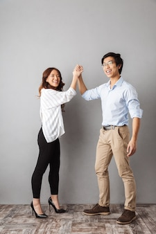 Full length of cheerful asian couple standing, giving high five