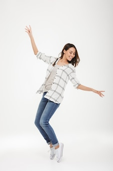 Full length cheerful brunette woman in shirt dancing over gray