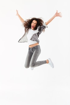 Full length cheerful curly woman jumping  and looking away over white wall