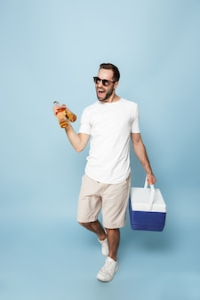Full length of a cheerful excited man wearing blank t-shirt standing isolated over blue wall, carrying cooler with cold beer
