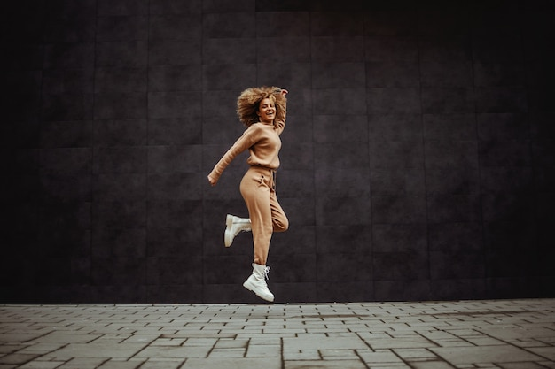 Full length of cheerful hip hop girl in tracksuit jumping in place
